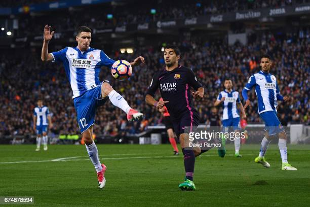 Aaron Martin of RCD Espanyol competes for the ball with Luis Suarez of FC Barcelona during the La Liga match between RCD Espanyol and FC Barcelona at...