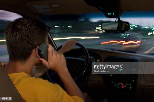 Aaron Mitchell uses his cellular phone while driving through traffic July 18 2000 in Prince Frederick MD Federal authorities fear the use of devices...