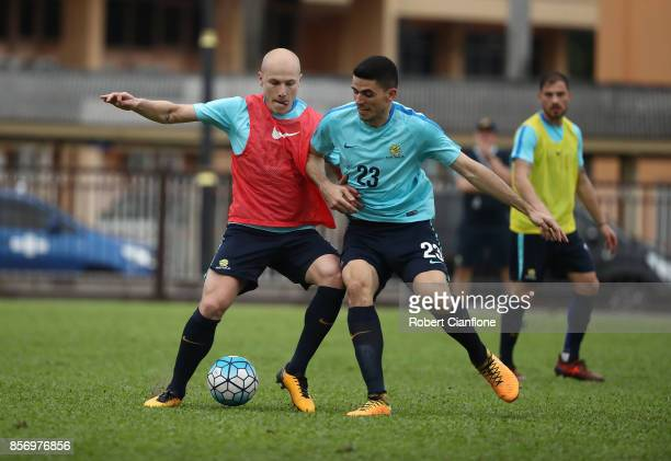Aaron Mooy and Tom Rogic of Australia compete for the ball during an Australia Socceroos training session at Hang Tuah Stadium on October 3 2017 in...