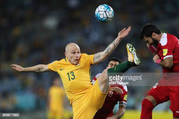 Aaron Mooy of Australia and Tamer Mohamd of Syria compete for the ball during the 2018 FIFA World Cup Asian Playoff match between the Australian...