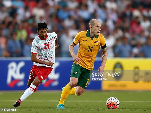 Aaron Mooy of Australia controls the ball as Manuchekhr Dzhalilov of Tajikistan closes in during the 2018 FIFA World Cup Qualifier match between the...