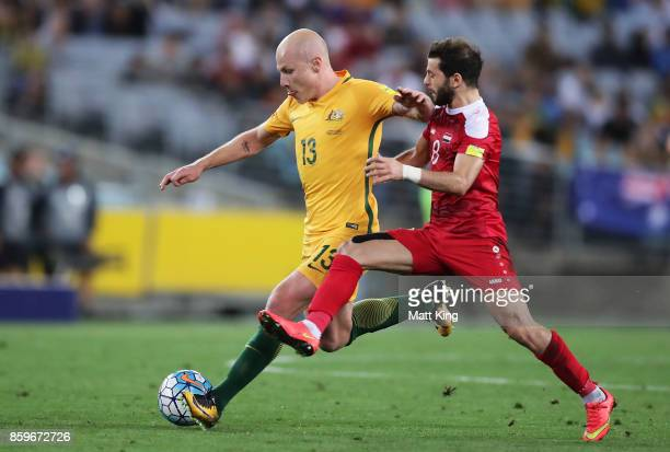 Aaron Mooy of Australia is challenged by Mahmoud Al Mawas of Syria during the 2018 FIFA World Cup Asian Playoff match between the Australian...