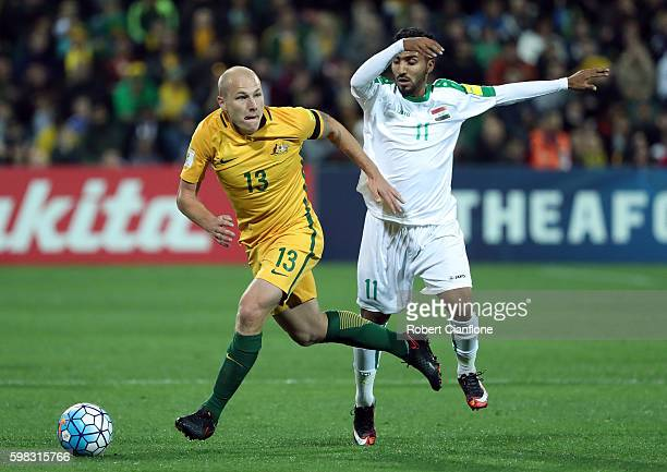 Aaron Mooy of Australia is chased by Ali Hisny Faisal of Iraq during the 2018 FIFA World Cup Qualifier match between the Australian Socceroos and...