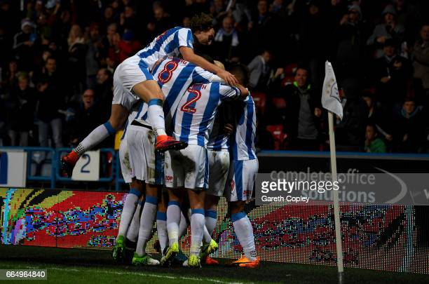 Aaron Mooy of Huddersfield celebrates with teammates after scoring his teams second goal during the Sky Bet Championship match between Huddersfield...