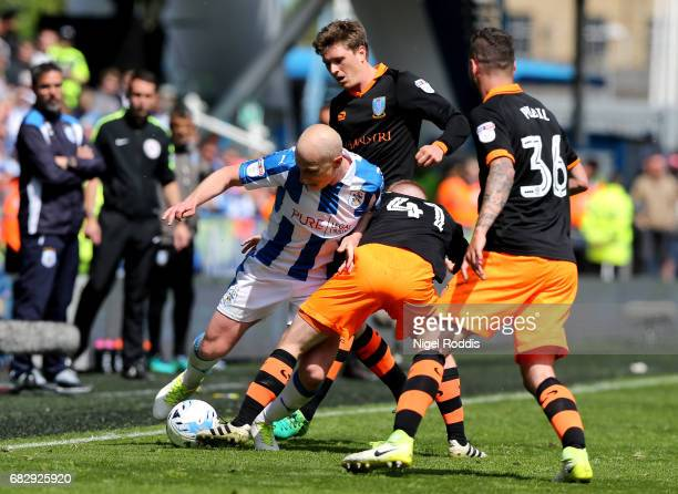 Aaron Mooy of Huddersfield Town attempts to hold off Barry Bannan of Sheffield Wednesday and Daniel Pudil of Sheffield Wednesday during the Sky Bet...