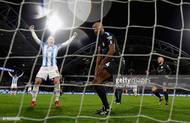 Aaron Mooy of Huddersfield Town celebrates after Nicolas Otamendi of Manchester City scored the first own goal as Vincent Kompany of Manchester City...