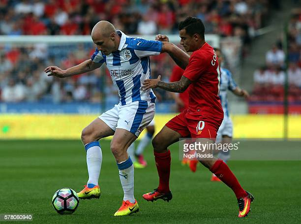 Aaron Mooy of Huddersfield Town challenged by Philippe Coutinho of Liverpool during the PreSeason Friendly match between Huddersfield Town and...