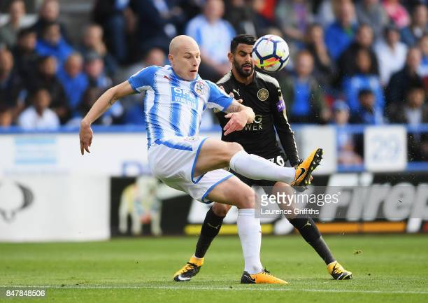 Aaron Mooy of Huddersfield Town is put under pressure from Riyad Mahrez of Leicester City during the Premier League match between Huddersfield Town...