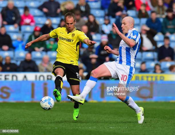 Aaron Mooy of Huddersfield Town is tackled by Luke Varney of Burton Albion during the Sky Bet Championship match between Huddersfield Town and Burton...