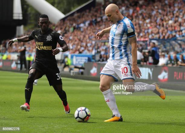 Aaron Mooy of Huddersfield Town passes the ball watched by Christian Atsu during the Premier League match between Huddersfield Town and Newcastle...
