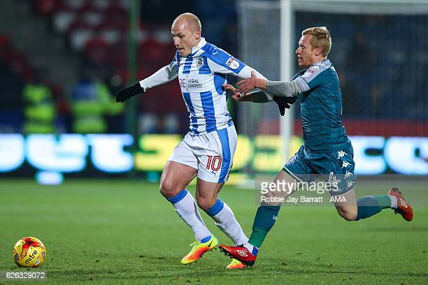 Aaron Mooy of Huddersfield Town under pressure from David Perkins of Wigan Athletic during the Sky Bet Championship match between Huddersfield Town...