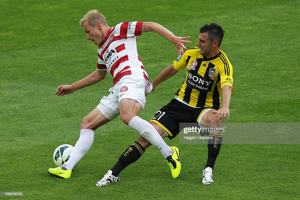 Aaron Mooy of the Wanderers is tackled by Dani Sanchez of the Phoenix during the round 16 A-League match between the Wellington Phoenix and the Western Sydney Wanderers at Westpac Stadium on January 13, 2013 in Wellington, New Zealand.