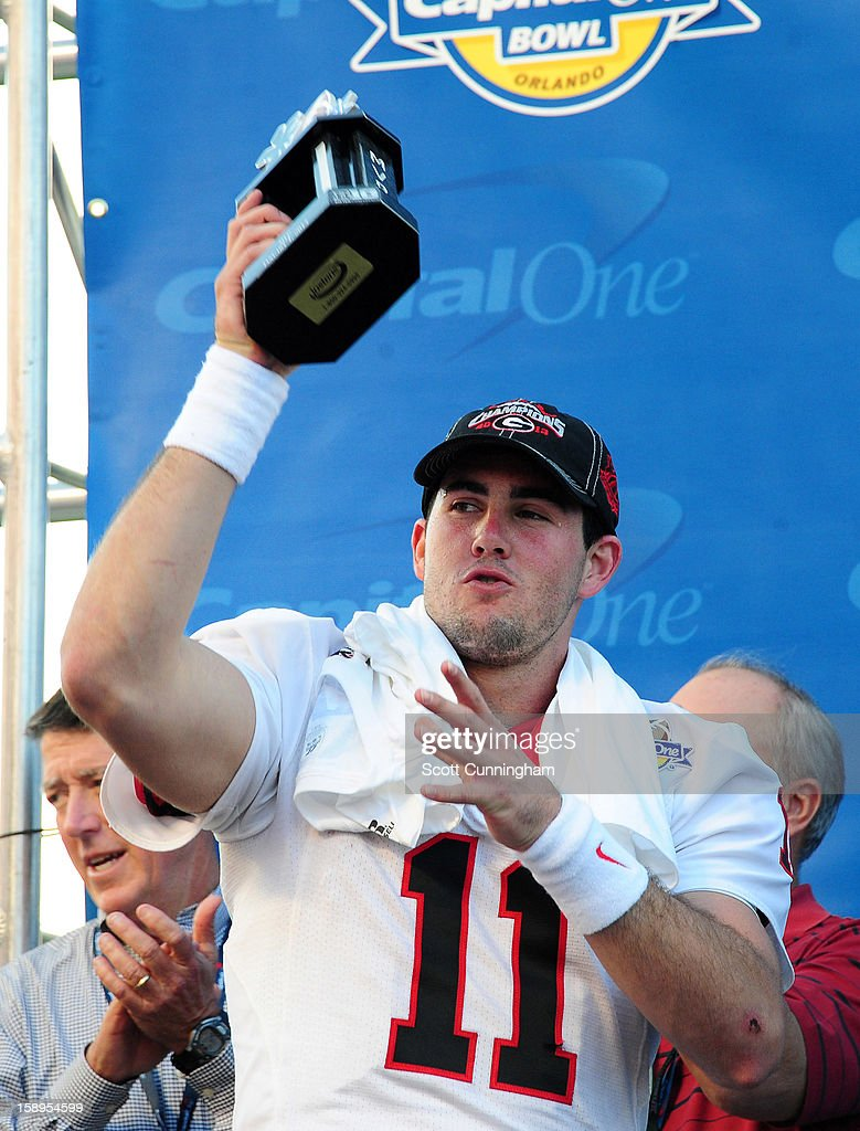 Aaron Murray #11 of the Georgia Bulldogs is awarded the Most Valuable Player trophy after the Capital One Bowl against the Nebraska Cornhuskers at the Citrus Bowl on January 1, 2013 in Orlando, Florida.