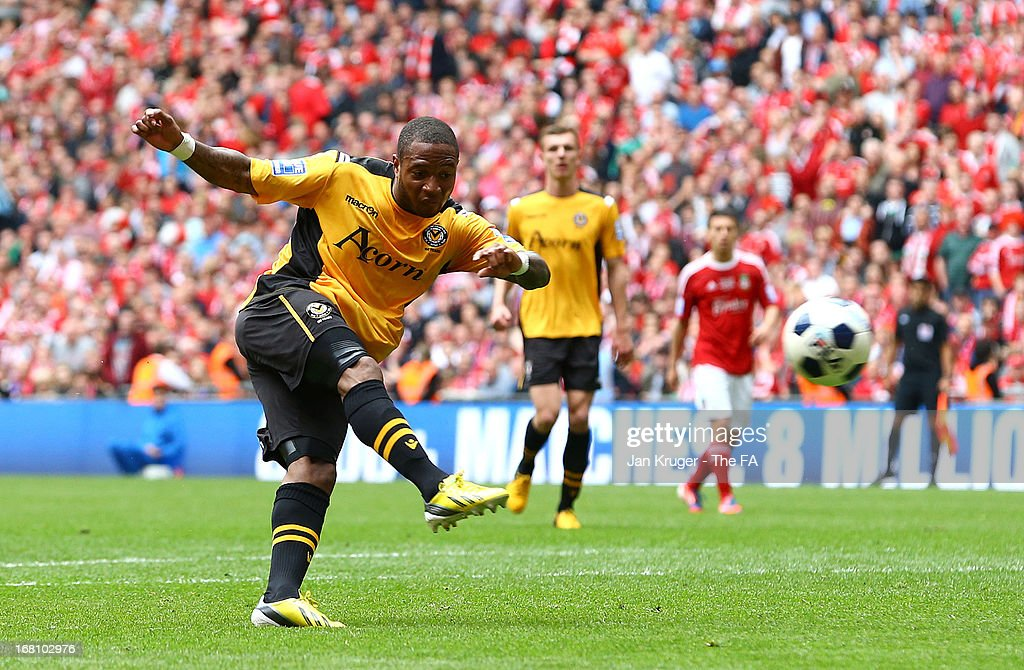 Aaron O'Connor of Newport County shoots past Daniel Davine to score a goal during the Conference Premier play-off final match between Wrexham and Newport County at Wembley Stadium on May 5, 2013 in London, England.
