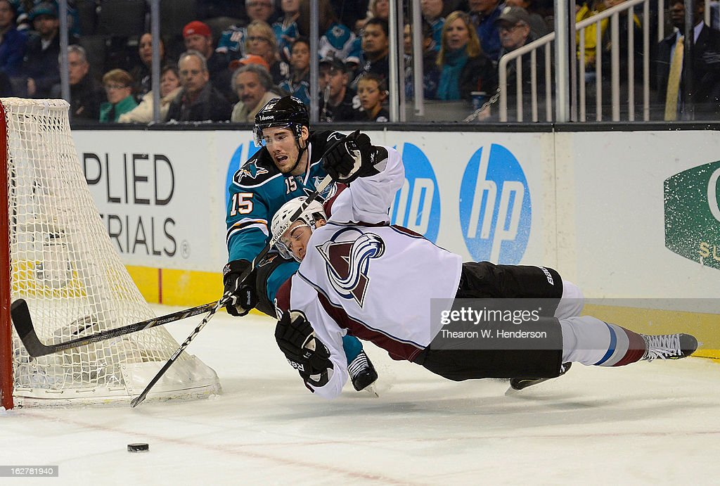 Aaron Palushaj #17 of the Colorado Avalanche falls to the ice attempting to maintain control of the puck away from James Sheppard #15 of the San Jose Sharks in the first period at HP Pavilion on February 26, 2013 in San Jose, California.