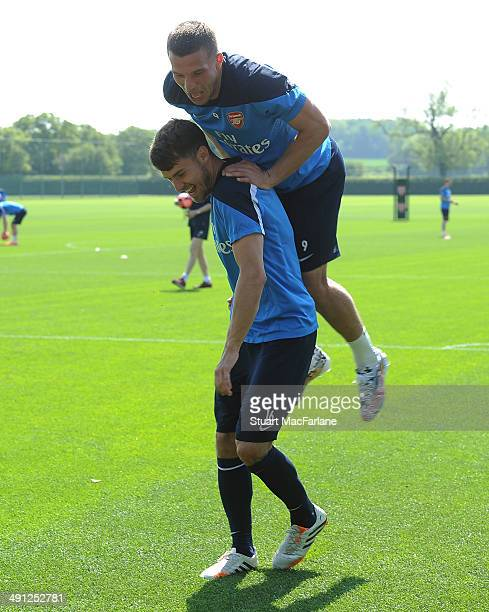 Aaron Ramsey and Lukas Podolski of Arsenal joke around after a training session at London Colney on May 16 2014 in St Albans England