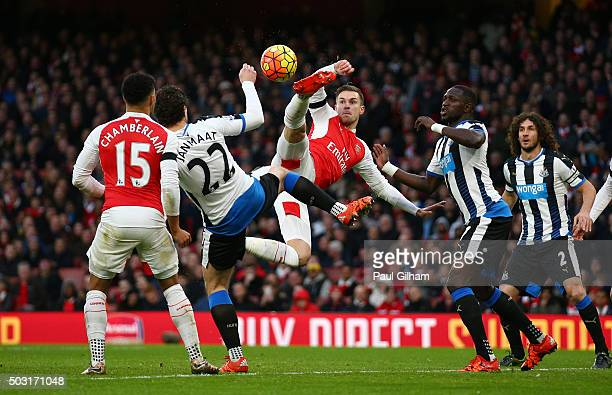 Aaron Ramsey of Arsenal and Daryl Janmaat of Newcastle United compete for the bacompete for the ballduring the Barclays Premier League match between...