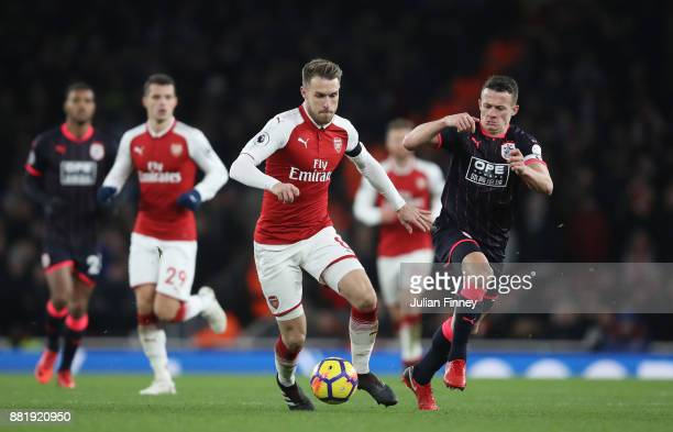 Aaron Ramsey of Arsenal attempts to get away from Jonathan Hogg of Huddersfield Town during the Premier League match between Arsenal and Huddersfield...