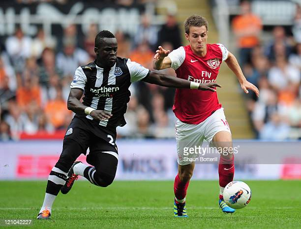 Aaron Ramsey of Arsenal battles for the ball with Cheik Tiote of Newcastle United during the Barclays Premier League match between Newcastle United...