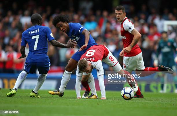 Aaron Ramsey of Arsenal battles with Willian and N'Golo Kante of Chelsea during the Premier League match between Chelsea and Arsenal at Stamford...