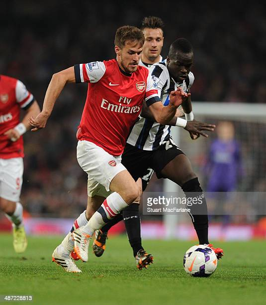 Aaron Ramsey of Arsenal breaks past Cheick Tiote of Newcastle during the Barclays Premier League match between Arsenal and Newcastle United at...
