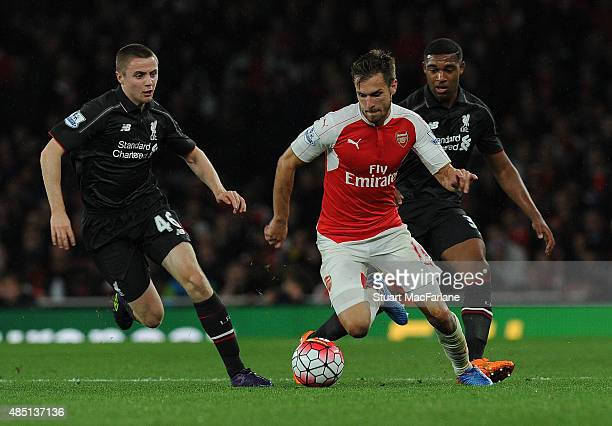 Aaron Ramsey of Arsenal breaks past Jordan Rossiter of Liverpool during the Barclays Premier League match between Arsenal and Liverpool on August 24...