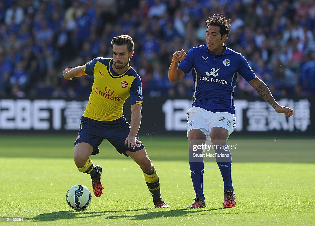 Aaron Ramsey of Arsenal breaks past Leonardo Ulloa of Leicester during the Barclays Premier League match between Leicester City and Arsenal at The King Power Stadium on August 31, 2014 in Leicester, England.