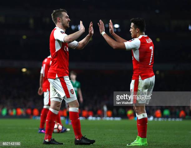 Aaron Ramsey of Arsenal celebrates scoring his sides fifth goal with Alexis Sanchez of Arsenal during The Emirates FA Cup QuarterFinal match between...