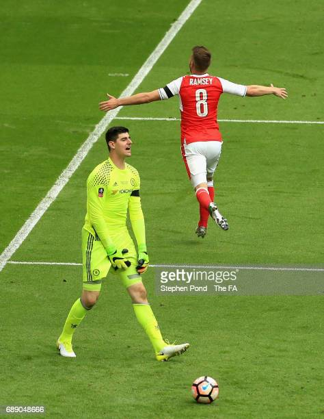 Aaron Ramsey of Arsenal celebrates scoring his sides second goal as Thibaut Courtois of Chelsea is dejected during the Emirates FA Cup Final between...
