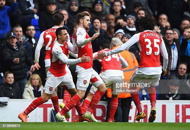 Aaron Ramsey of Arsenal celebrates scoring his team's first goal with his team mates during the Barclays Premier League match between Tottenham...
