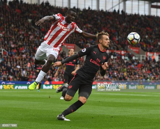 Aaron Ramsey of Arsenal challenged by Mame Diouf of Stoke during the Premier League match between Stoke City and Arsenal at Bet365 Stadium on August...