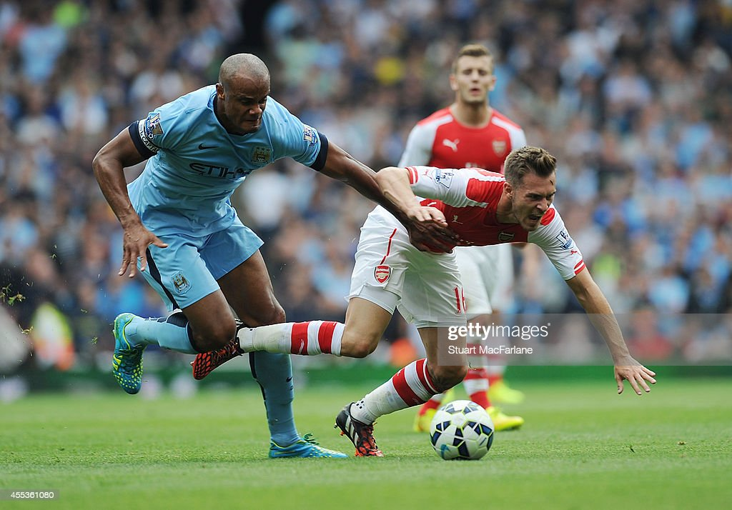 Aaron Ramsey of Arsenal challenged by Vincent Kompany of Manchester City during the Barclays Premier League match between Arsenal and Manchester City at Emirates Stadium on September 13, 2014 in London, England.