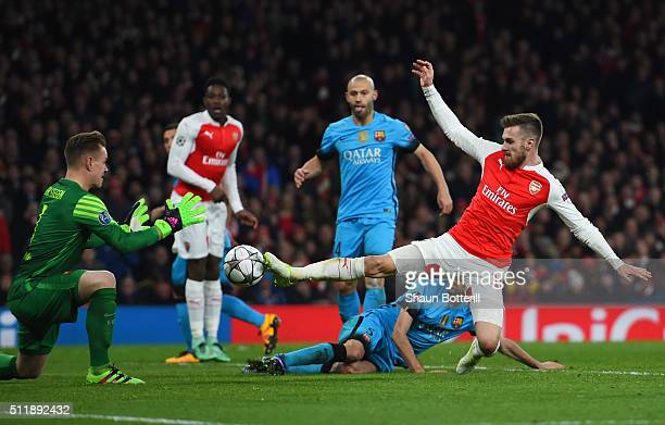 Aaron Ramsey of Arsenal competes for the ball with goalkeeper MarcAndre ter Stegen and Sergio Busquets of Barcelona during the UEFA Champions League...