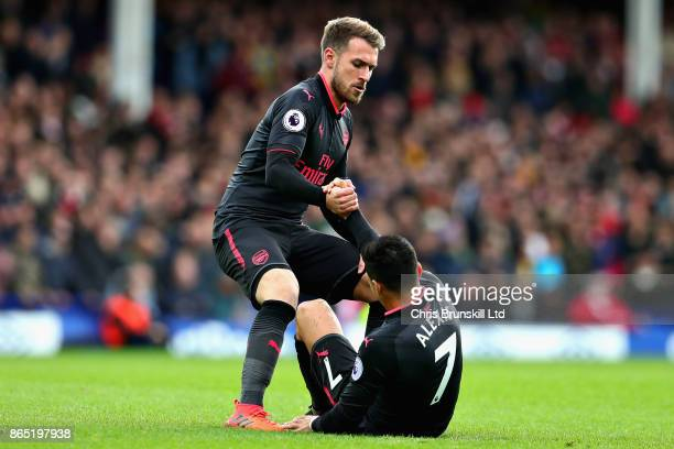 Aaron Ramsey of Arsenal helps Alexis Sanchez of Arsenal up from the ground during the Premier League match between Everton and Arsenal at Goodison...