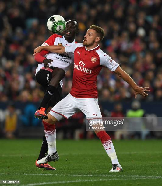 Aaron Ramsey of Arsenal is challenged by Abraham Majok of Western Wanderers during the match between the Western Sydney Wanderers and Arsenal FC at...