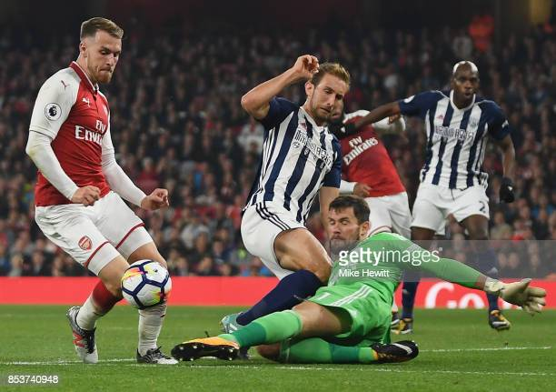 Aaron Ramsey of Arsenal is challenged by goalkeeper Ben Foster of West Bromwich Albion during the Premier League match between Arsenal and West...