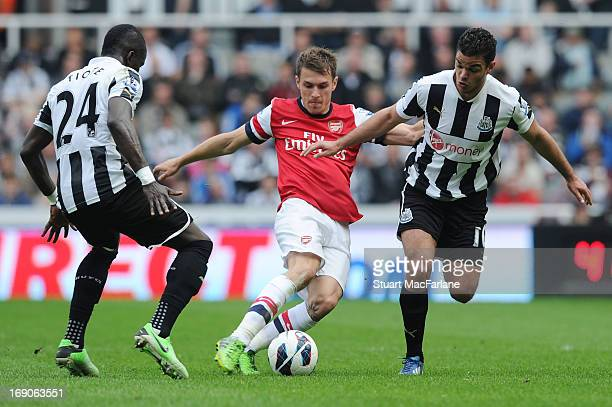 Aaron Ramsey of Arsenal is challenged by Hatem Ben Arfa and Cheick Tiote of Newcastle during the Barclays Premier League match between Newcastle...