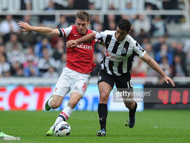 Aaron Ramsey of Arsenal is challenged by Hatem Ben Arfa of Newcastle during the Barclays Premier League match between Newcastle United and Arsenal at...