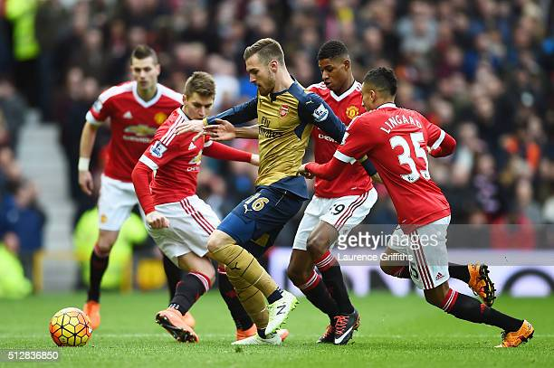 Aaron Ramsey of Arsenal is closed down by Marcus Rashford of Manchester United during the Barclays Premier League match between Manchester United and...