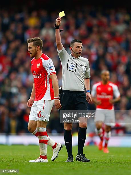 Aaron Ramsey of Arsenal is shown a yellow card by referee Michael Oliver during the Barclays Premier League match between Arsenal and Chelsea at...