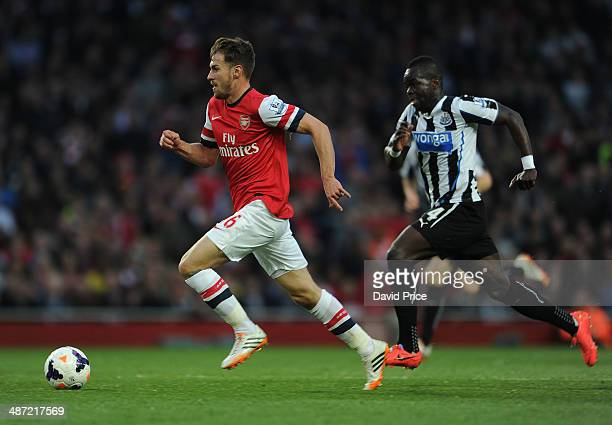 Aaron Ramsey of Arsenal races away from Cheick Tiote of Newcastle during the match between Arsenal and Newcastle United in the Barclays Premier...