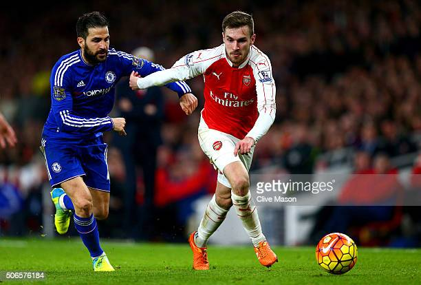 Aaron Ramsey of Arsenal runs with the ball under pressure from Cesc Fabregas of Chelsea during the Barclays Premier League match between Arsenal and...