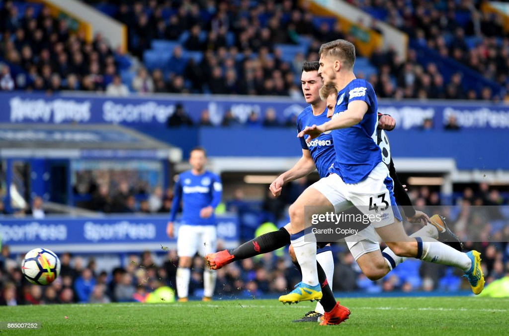 Aaron Ramsey of Arsenal scores his sides fourth goal while under pressure from Phil Jagielka of Everton and Jonjoe Kenny of Everton during the Premier League match between Everton and Arsenal at Goodison Park on October 22, 2017 in Liverpool, England.