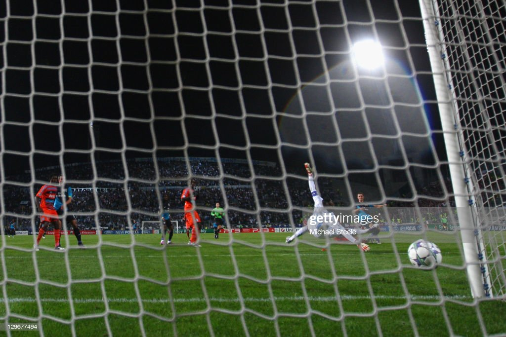 Aaron Ramsey (R) of Arsenal scores the winning goal in injury time past the dive of goalkeeper Steve Mandanda during the UEFA Champions League Group F match between Olympique de Marseille and Arsenal FC at Stade Velodrome on October 19, 2011 in Marseille, France.