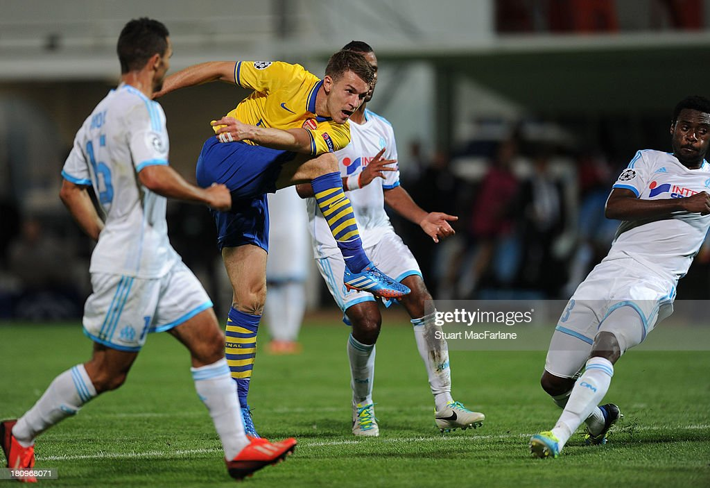 Aaron Ramsey of Arsenal shoots through the Marseille defence to score his team's second goal during the UEFA Champions League match between Olympique de Marseille and Arsenal at Stade Velodrome on September 18, 2013 in Marseille, France.