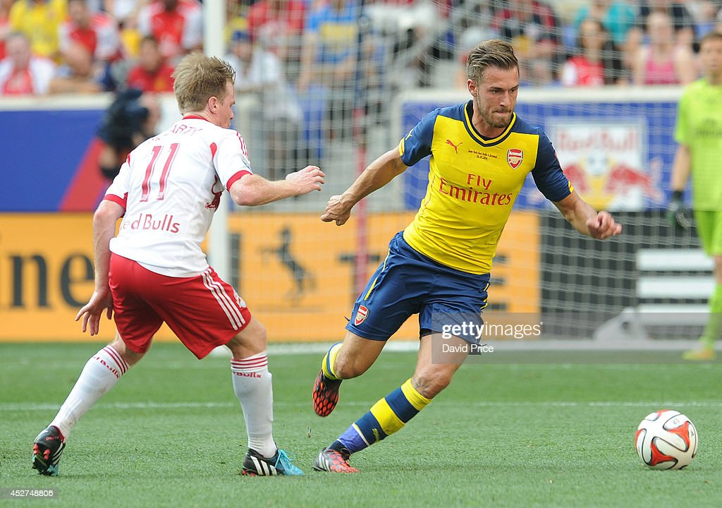 <a gi-track='captionPersonalityLinkClicked' href=/galleries/search?phrase=Aaron+Ramsey&family=editorial&specificpeople=4784114 ng-click='$event.stopPropagation()'>Aaron Ramsey</a> of Arsenal skips past <a gi-track='captionPersonalityLinkClicked' href=/galleries/search?phrase=Dax+McCarty&family=editorial&specificpeople=4233641 ng-click='$event.stopPropagation()'>Dax McCarty</a> of New York Red Bulls during the pre season match between New York Red Bulls and Arsenal at Red Bull Arena on July 26, 2014 in Harrison, New Jersey.