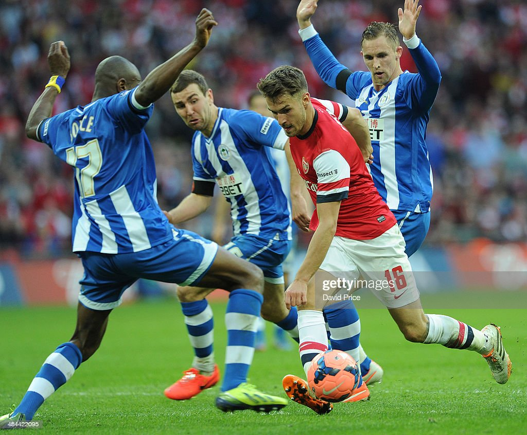 Aaron Ramsey of Arsenal takes on Emerson Boyce James McArthur and Jack Collison of Wigan during the match between Arsenal and Wigan Athletic in the...