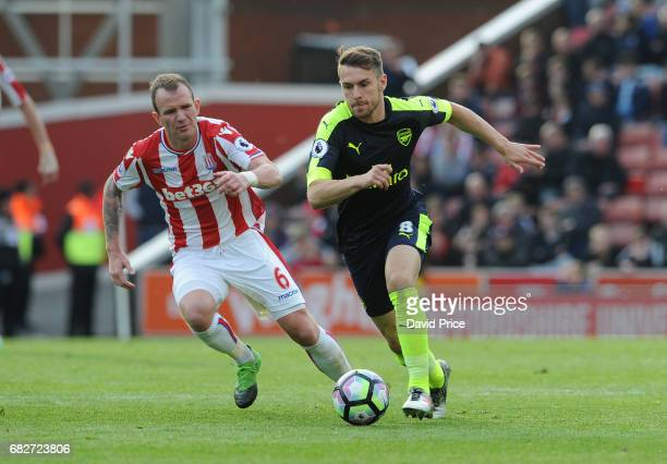 Aaron Ramsey of Arsenal takes on Glenn Whelan of Stoke during the Premier League match between Stoke City and Arsenal at Bet365 Stadium on May 13...
