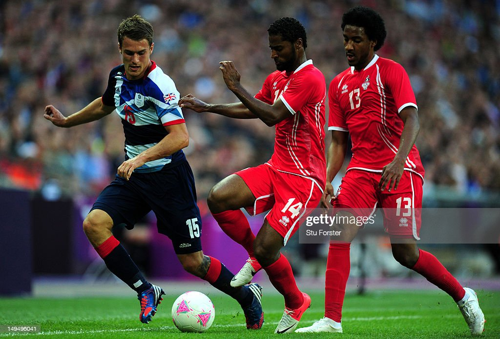 Aaron Ramsey of Great Britain controls the ball ahead of Abdelaziz Sanqour and Khamis Esmaeel of United Arab Emirates during the Men's Football first round Group A Match between Great Britain and United Arab Emirates on Day 2 of the London 2012 Olympic Games at Wembley Stadium on July 29, 2012 in London, England.