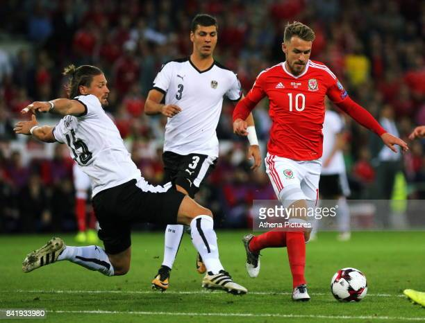 Aaron Ramsey of Wales charges forward past Sebastian Prodl and Aleksandar Dragovic of Austria during the FIFA World Cup Qualifier Group D match...